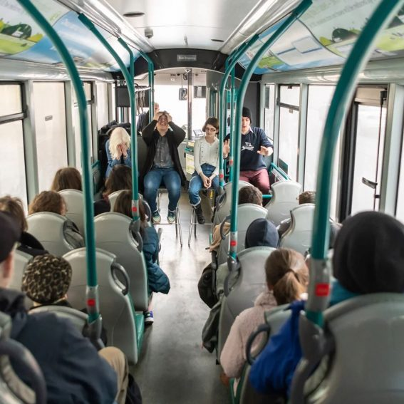 """Live Photo of """"The 900 Club"""": four people perform in front of an audience seated on a bus. Photo taken at UK Young Artists Festival in Nottingham.."""