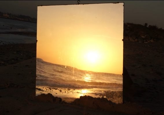 """Still from """"Parts of the Day"""": the reflection of sun setting over the sea in a mirror"""