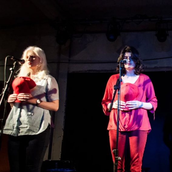 """Live photo of """"A Matter of Time"""": two women on a stage, both holding red baseball caps and apparently lost in thought."""