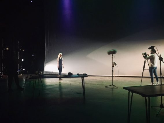"""Behind the scenes of """"Within Sight"""" filming. Ellen Renton, wearing blue running clothes, is being filmed while standing on a stage in front of a white backdrop."""