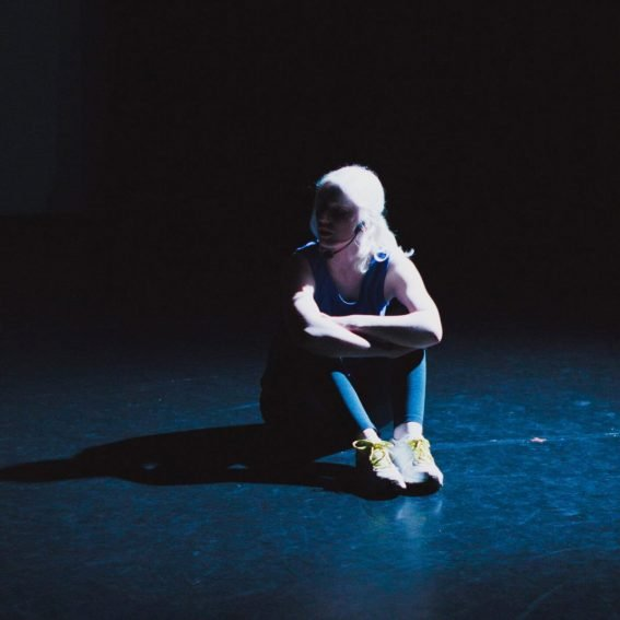 """Live Photo of """"Within Sight"""": a woman with albinism in blue running clothes is sitting in the centre of a blank, dark stage, shadows obscuring her face."""