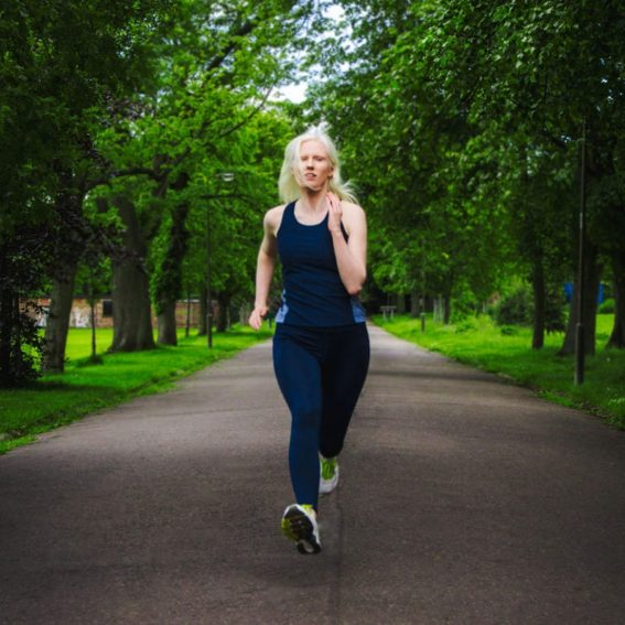 """""""Within Sight"""" publicity shot. A woman with albinism in blue running clothes is running down a tree-lined park path towards the camera."""