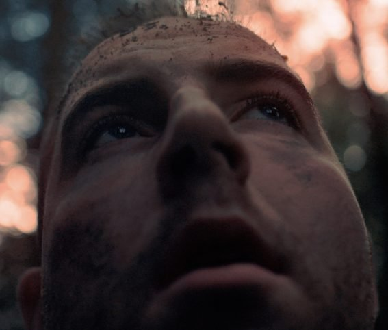 """Still from """"What Athena Saw When Tiresias Looked"""": close up of a man's face, looking upward and appearing fearful. An out-of-focus forest surrounds him"""
