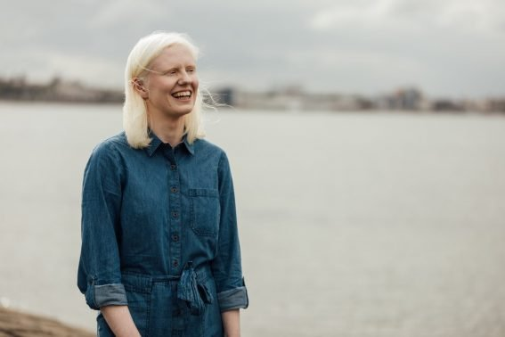 Ellen Renton, standing with her body at a diagonal angle to the camera. She is laughing, and standing in front of an out-of-focus Firth of Forth.