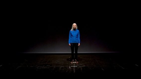 Within Sight live performance photo: Ellen , with her hair down, wearing a bright blue running jacket and dark leggings. She is standing centre stage against a black background, she is looking calmly straight at the camera